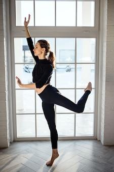 창 근처 거실에서 발레, 춤, 체조를하는 여자