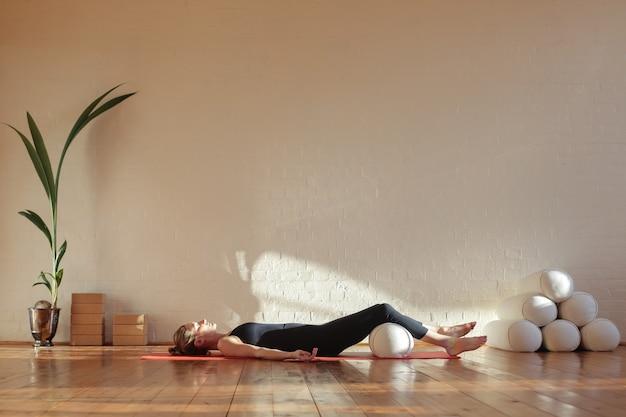 Женщина делает дыхательные упражнения в шавасане