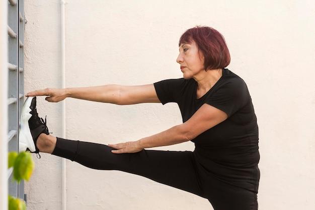 Женщина делает кардио и опираясь с ногой на стене