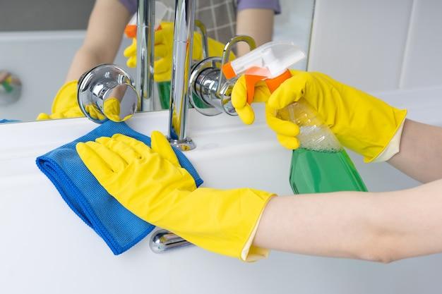 Женщина делает работу по дому в ванной, чистит ванну с помощью спрея и ткани Premium Фотографии