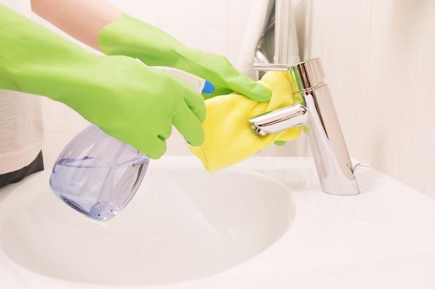 Женщина делает работу по дому в ванной, чистит раковину и кран с распылителем.
