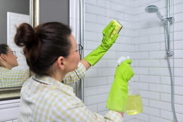 집에서 욕실에서 청소를 하는 여자. 스폰지와 세제 여성 세척 샤워 유리입니다.
