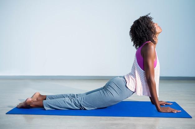 Woman doing cobra pose on exercise mat