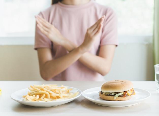Женщина делает знак креста, чтобы отказаться от нездоровой пищи (гамбургер и картофель, жареный), у которых есть ma