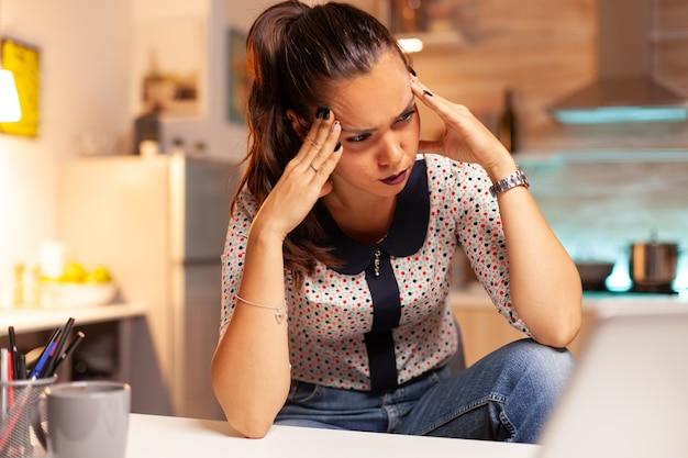 夜間に頭痛を感じて難しいオンラインコンピュータ作業をしている女性。深夜に最新のテクノロジーを使用して、仕事、ビジネス、キャリア、ネットワーク、ライフスタイル、ワイヤレスで残業している従業員。