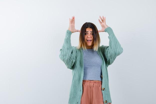 Женщина делает уши жест в повседневной одежде и с тревогой смотрит. передний план.