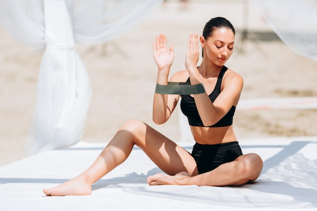 Woman doing exercise for her hands with a tape in the park outdoor.