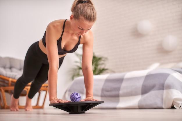 Женщина делает упражнения на специальном симуляторе балансировки. блондинка спортивная спортивная одежда, дома сделал упражнение укрепляет мышцы.