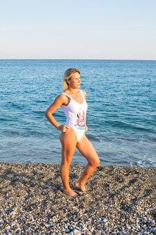 Женщина делает упражнения на пляже
