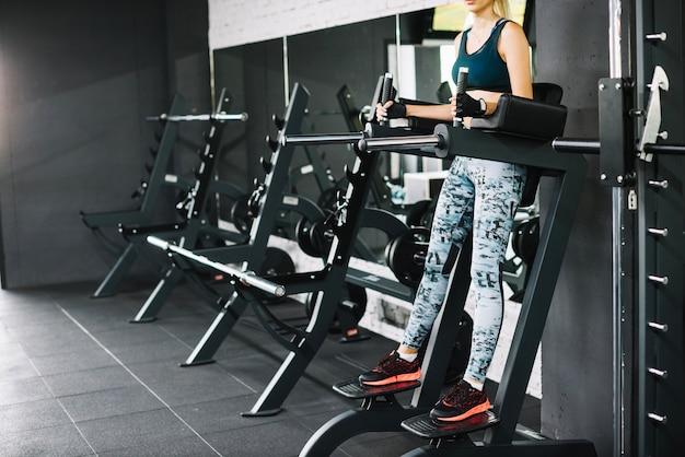 체육관에서 시뮬레이터에 운동을하는 여자