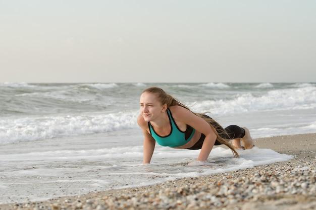 Женщина делает упражнения на пляже, волны на заднем плане
