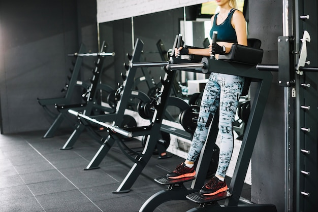 Woman doing exercise on simulator in gym