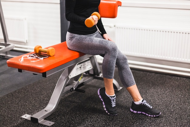 Woman doing exercise with dumbbell at fitness center