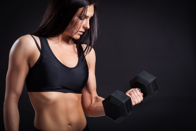 Woman doing an exercise with a  dumbbell