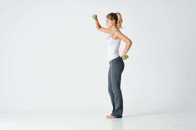 Женщина делает упражнения в спортивной одежде на свету в помещении