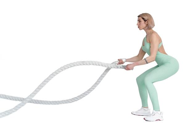 バトルロープでエクササイズをしている女性。白い壁に分離されたスポーツウェアの筋肉モデルの写真。強さとモチベーション。