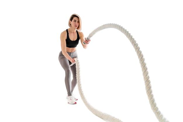 Женщина делает упражнения с боевыми веревками