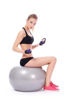Женщина делает упражнения с гантелями на фитнес-мяч