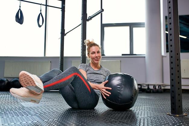 フィットネスジムクラスでアブスと演習を行う女性。コア腹部の筋肉を引き付ける。女性の健康的なライフスタイルのイメージコンセプト。