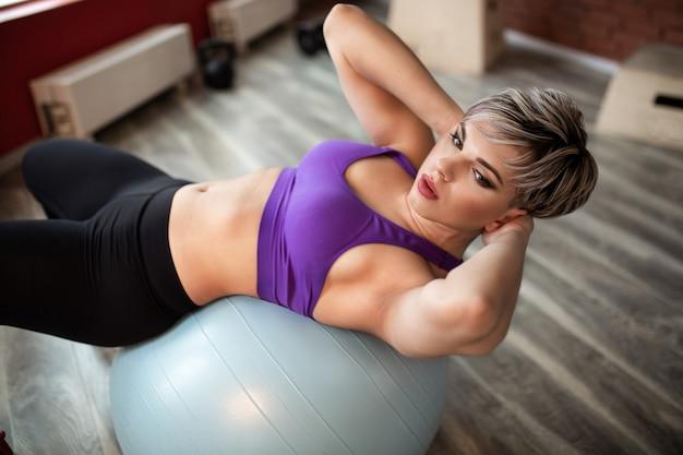피트 니스 체육관 클래스에서 fitball와 함께 운동을하는 여자