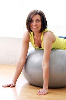 Donna che fa le esercitazioni con la sfera relativa alla ginnastica