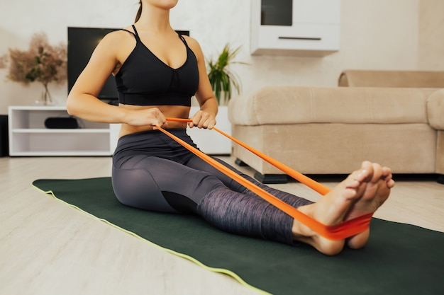 Woman doing exercises with resistance bands at home. cropped shot of a young woman exercising with an elastic band on the floor.