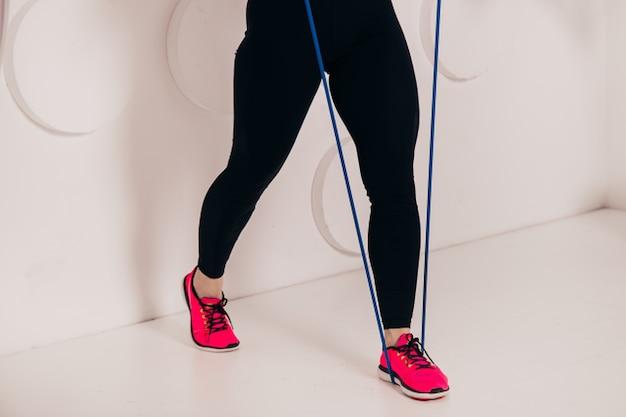 Женщина делает упражнения с группами сопротивления, спортивная концепция здорового образа жизни