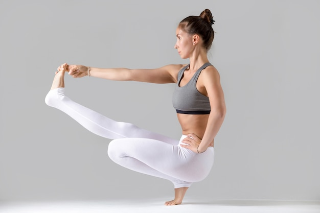 Woman doing extended hand to big toe pose with squat