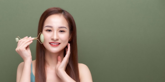 스파 스킨 케어 치료를 위해 옥 페이셜 롤러로 얼굴 마사지를 하는 여성