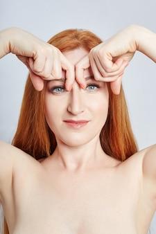 フェイシャルマッサージ、体操、マッサージライン、プラスチック製の口の目と鼻をしている女性。マッサージテクニック