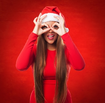 Woman doing finger glasses in a red background