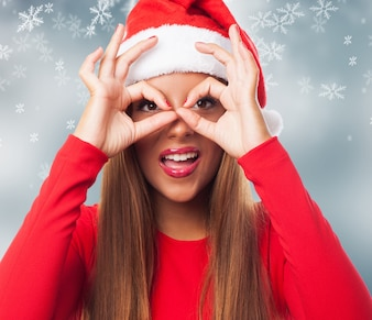 Woman doing finger glasses in a snowflakes background