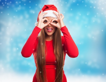 Woman doing finger glasses while snowing