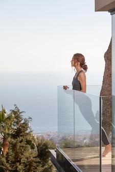 バルコニーで自宅でフィットネスをしている女性