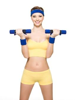 Женщина делает фитнес-упражнения с гантелями, изолированными на белом