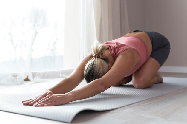 Женщина делает фитнес-упражнения и растяжку