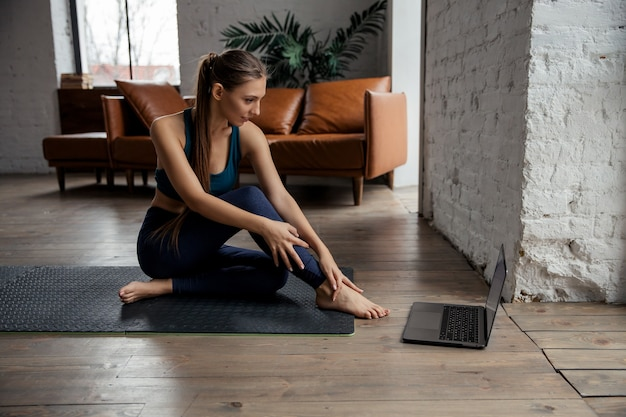 Woman doing fitness exercises on mat opposite laptop at home. wellness and healthy lifestyle concept. . high quality photo. high quality photo