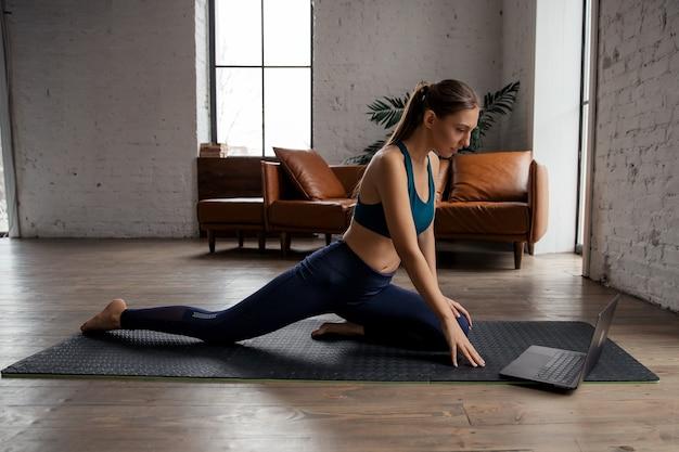 Женщина делает фитнес-упражнения на коврике напротив ноутбука дома. концепция благополучия и здорового образа жизни. . фото высокого качества