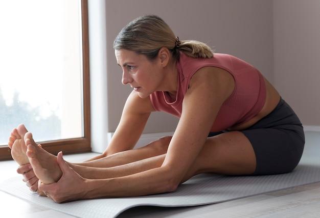 Женщина делает фитнес-упражнения боком