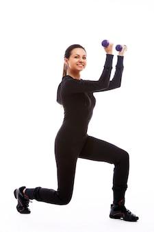 Женщина делает фитнес-упражнения с весами