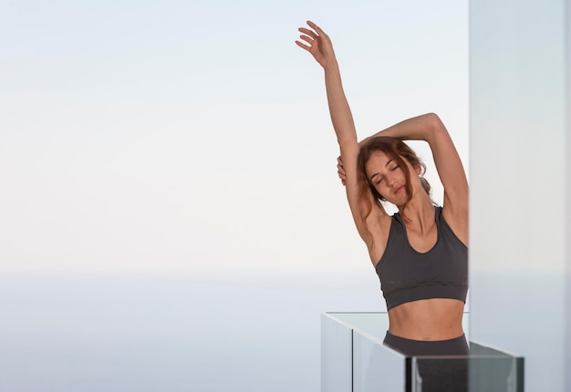 Woman doing fitness at home on balcony