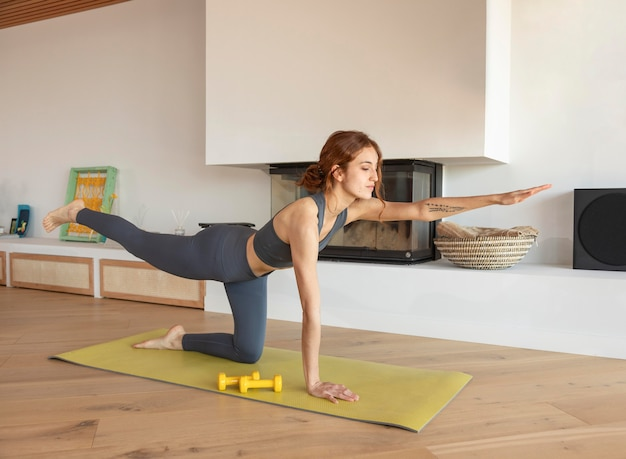Woman doing fitness at home with weights