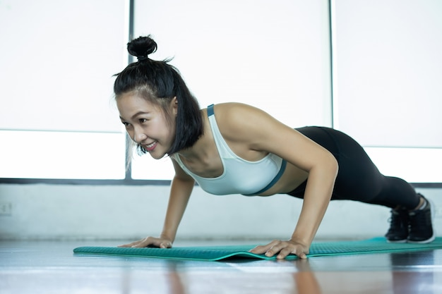 Woman doing fitness training. fitness woman doing push ups on a training mat. young woman doing push-ups at the gym. muscular female doing pushups on exercise mat at gym.