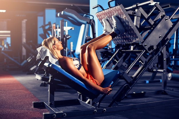 Woman doing fitness training on a leg extension push machine with weights