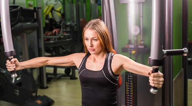 Женщина делает фитнес-тренировку на машине-бабочке с весами в тренажерном зале.