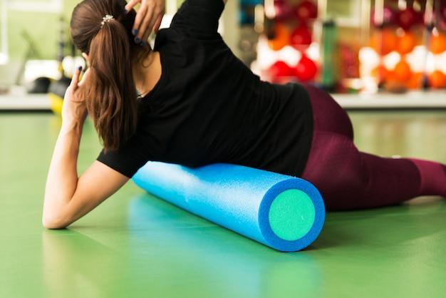 Женщина делает упражнения ролика пены на полу в тренажерном зале