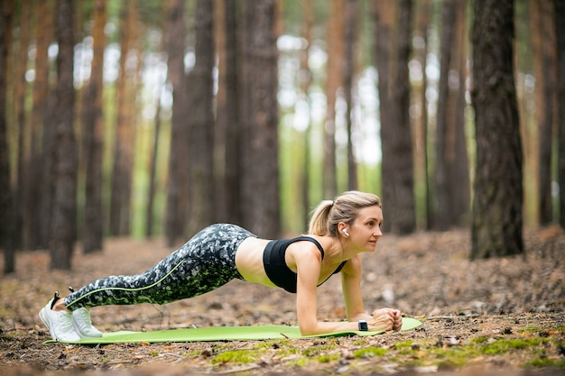 Woman doing forearm plank pose outdoors in forest on fresh air