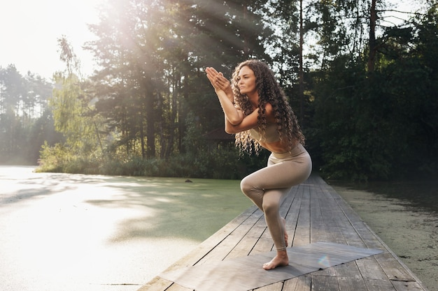 Woman doing garudasana exercise eagle pose on a wooden bridge on a summer morning in the park