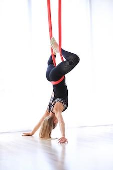赤いリネンで体操のピラティスをやっている女性