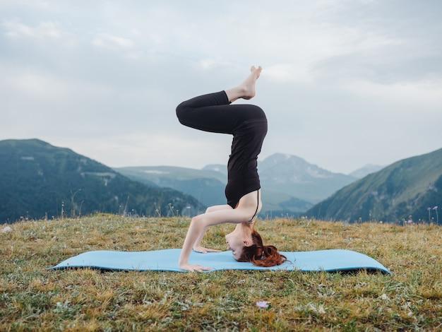 体操をしている女性は山の自然のヨガを行使します